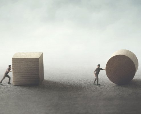 Image of person rolling a round sphere vs a square block